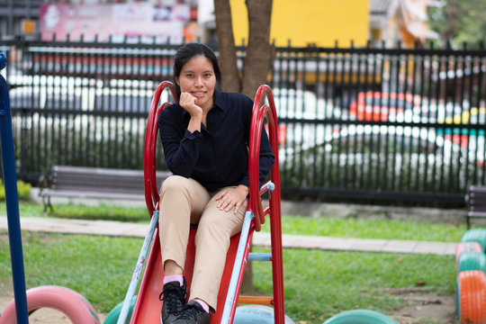 Portrait Of Woman Sitting On Slide In Playground