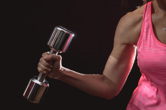 Midsection Of Woman Exercising With Dumbbell Against Black Background