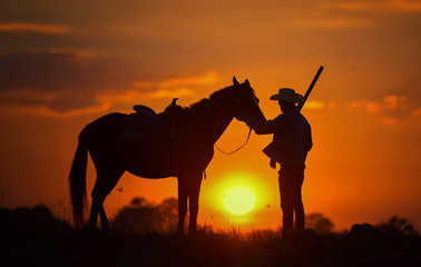 Foto auf Acrylglas Rotglühen Cowboy silhouette And horses in the evening, sunset