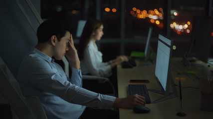 Asian man working late sitting on desk in office overtime at night. Business man feeling tired and stress for overload job hand on nose