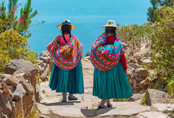 Two indigenous Quechua women in traditional clothes walking down the path to the harbor of Isla Taquile (Taquile Island) with the Titicaca Lake in the background, Peru. Fototapete