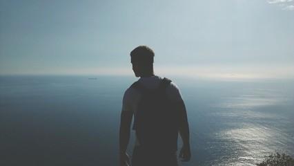 Fototapeta Rear View Of A Man Overlooking Sea