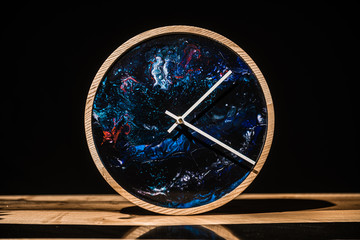 Round eco clock made of wood and epoxy. The subject of interior in your home. Natural handmade tree. Clock on the background.
