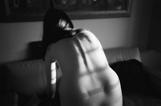 Rear View Of Naked Woman Bending Over In Living Room