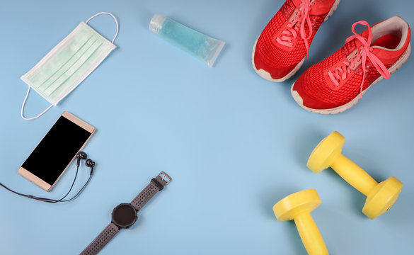 flat lay of sports accessories with hygienic protective mask and alcohol sanitizer hand gel on blue background ,protection from corona virus or COVID-19 during exercise  concept.