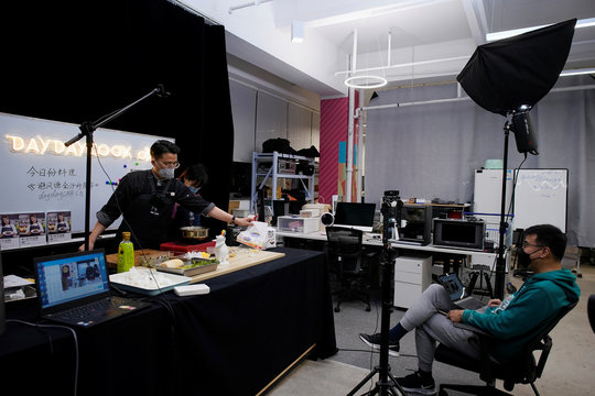A chef wearing a face mask conducts a cooking lesson through a live-streaming session inside a restaurant at a office as the country is hit by an outbreak of the novel coronavirus that can cause COVID-19 disease, in Shanghai