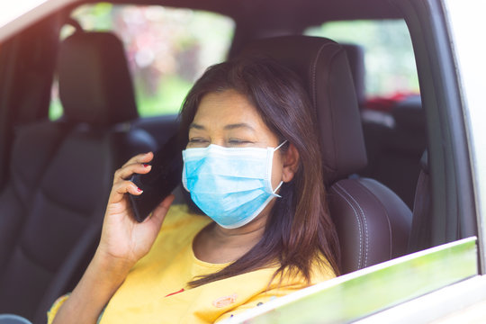 Covid-19 and Air pollution pm2.5 concept.Indian woman read coronavirus news in truck car wearing mask for protect virus and pm2.5.Wuhan coronavirus and epidemic virus symptoms.