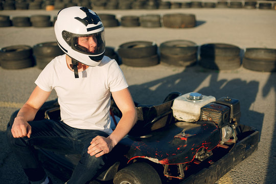 Karting. Man in a white t-shirt. Male with a kart car
