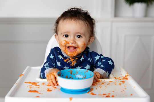 Happy baby in high chair eating carrot puree with messy face
