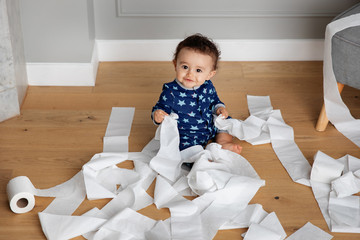 Smiling baby playing with toilet paper on wooden floor Fotobehang