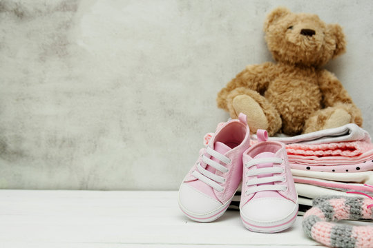 Pink baby girl shoes, newborn clothes and soft toys. Motherhood, education or pregnancy concept with copy space. Greeting card.