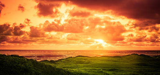 Foto op Plexiglas Europa Sonnenuntergang über dem Meer in einer Dünenlandschaft