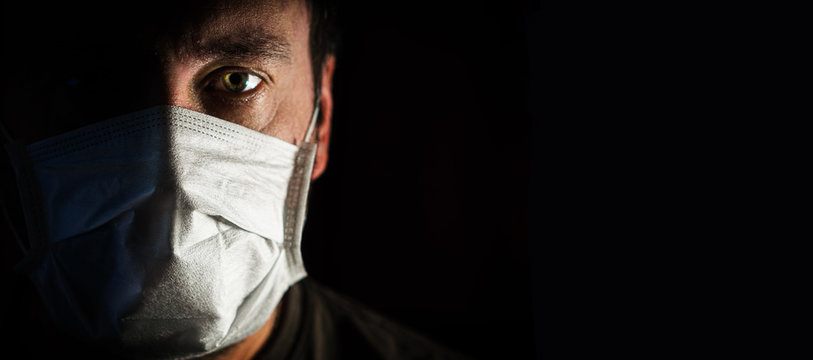 portrait of a man in a medical mask in a low key. a worldwide tragedy. COVID-19 virus pandemic warning