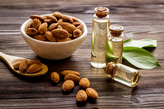 Spa and aromatherapy. Almond oil in small bottles on wooden background