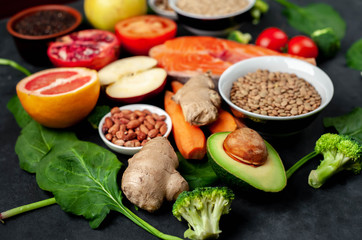 Selection of healthy food: salmon, fruits, seeds, cereals, superfoods, vegetables, leafy vegetables, eggs, rye bread on a stone background