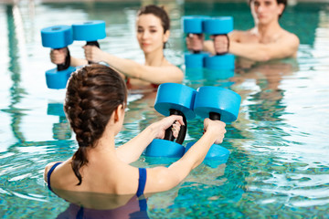 Selective focus of trainer holding barbells while exercising water aerobics with man and woman in swimming pool