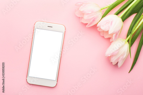 Mobile phone and spring flower pink tulips on the pink background. Theme of love, mother's day, women's day flat lay