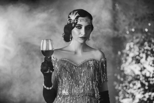 Black and white closeup portrait stylish retro woman in shine silver dress with glass of wine in hand. old finger wave hairstyle with headband. vintage holiday. backdrop bright smoke. Cat eyes makeup