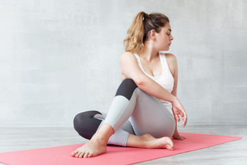 Lovely woman doing stretching or yoga exercise on a mat