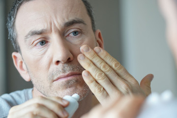Portrait of man applying cosmetics on his face Wall mural