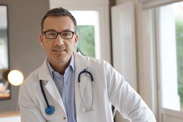 Portrait of doctor posing in office, looking at camera Fotobehang