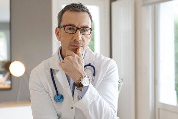 Portrait of doctor posing in office, looking at camera