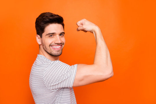 Profile photo of cool self-confident guy raise fist arm showing strong perfect shape biceps amazing training results wear striped t-shirt isolated vivid orange color background