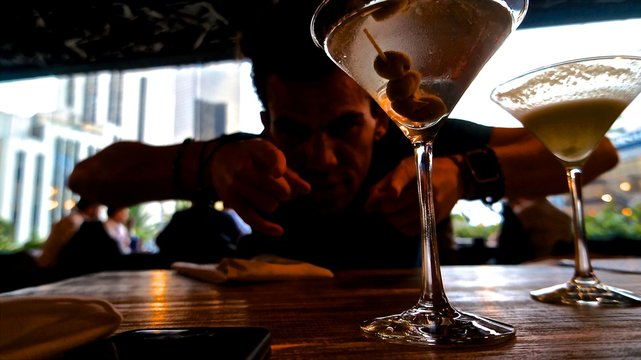 Man Pointing At Martini Glasses In Restaurant