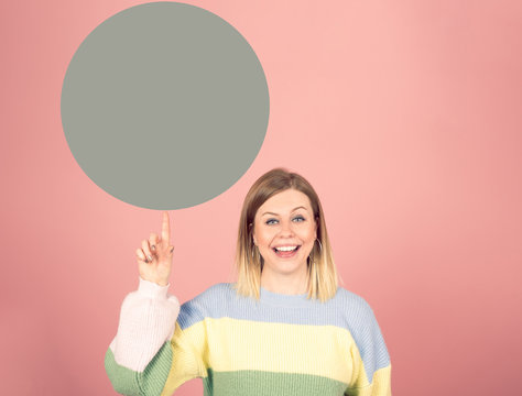 smiling toothy happy young woman pointing up the finger to a green circle