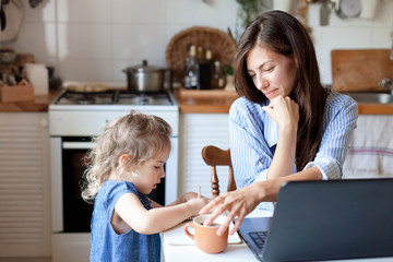 Working mom works from home office with kid. Woman and cute child using laptop. Freelancer...