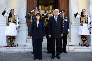 Outgoing Greek President Pavlopoulos shakes hands with newly sworn-in President Sakellaropoulou during a handover ceremony at the Presidential Palace