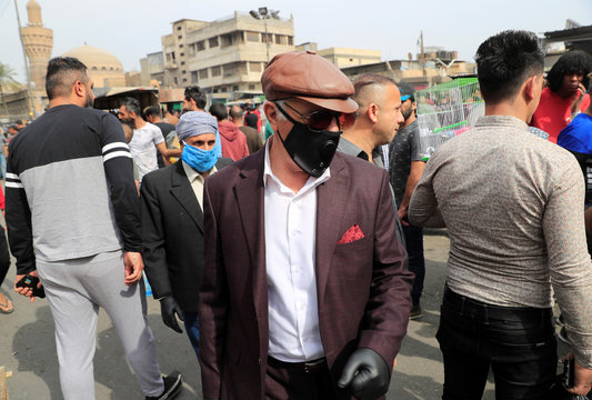 Iraqi men wearing protective masks, following the outbreak of coronavirus, as they walk at the Ghazal pet market in Baghdad