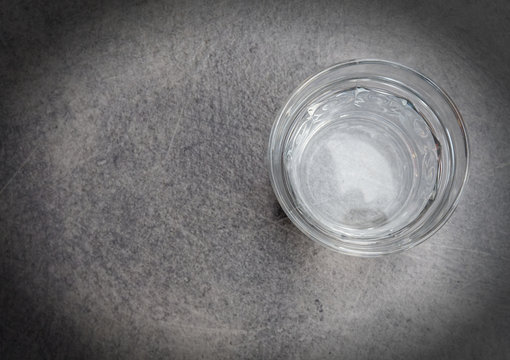 The glass is half full of water on grey table top view with space for text, filtered image
