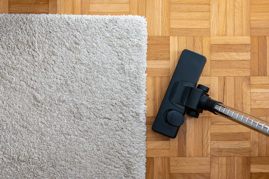Vacuum cleaner extension on a laminated wooden floor next to a grey fabric rug