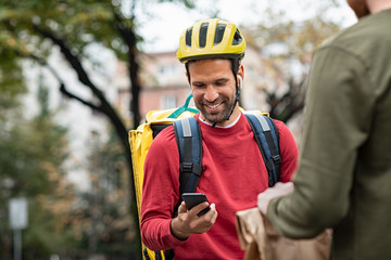 Delivery man checking food order with smartphone