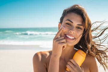 Smiling woman applying sunscreen