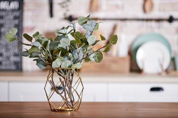 Obraz Metallic geometric decorative through vase with artificial eucalyptus branches on a wooden table. - fototapety do salonu