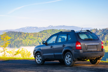 suv on the edge of a mountain. beautiful view in to the distant valley full of fog. ridge in the distance. fantastic springtime scenery in the morning. travel by car concept