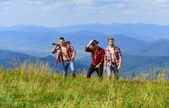 Enjoying freedom together. Group of young people in checkered shirts walking together on top of mountain. Hiking with friends. Friendly guys with guitar hiking on sunny day. Tourists hiking concept