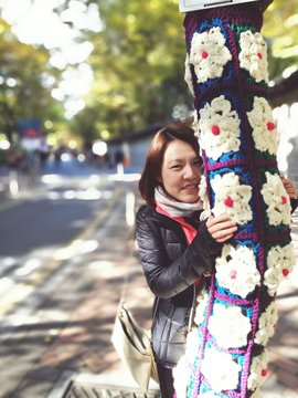 Portrait Of Young Woman Holding Yarn Bombing Tree Trunk At Park