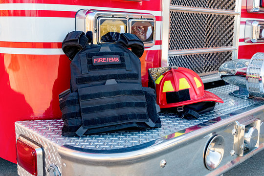 Ballistic vest and red firefighter helment on fire truck bumper. Concept of evolving role of fire department response to mass casualty shooting and terrorism