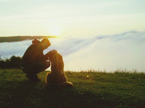 Man With Dog On Grassy Hill By Cloudscape