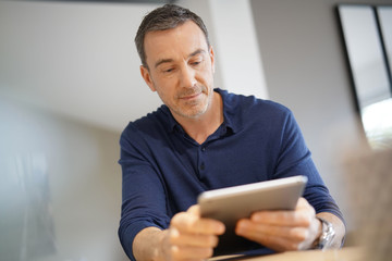 Portrait of middle-aged man connected on digital tablet Wall mural