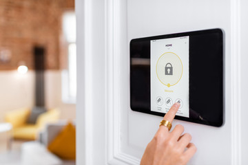 Obraz Controlling home alarm system with a digital touch screen panel installed on the wall. Concept of wireless secure control and smart home - fototapety do salonu