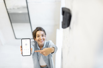 Woman controlling alarm system with a smart phone, showing phone with launched mobile application. View from above with motion sensor on the foreground Wall mural