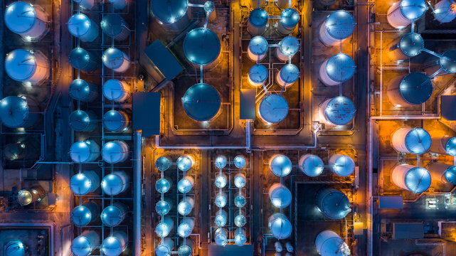 Aerial top view storage tank farm at night, Tank farm storage chemical petroleum petrochemical refinery product at oil terminal, Business commercial trade fuel and energy transport by tanker vessel.