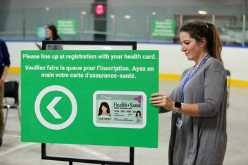 A worker places a sign as medical staff members prepare to receive patients for coronavirus screening at a temporary assessment center at the Brewer hockey arena in Ottawa