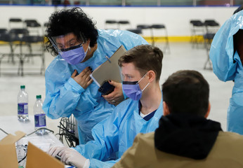 Medical staff members assess someone portraying the role of a patient as they prepare to receive people for coronavirus screening at a temporary assessment center at the Brewer hockey arena in Ottawa
