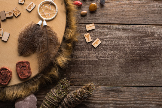 Top view of tambourine, dreamcatcher with smudge sticks and crystals on wooden background