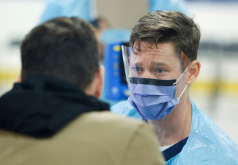 A medical worker assesses someone portraying the role of a patient as hospital staff prepare to receive people for coronavirus screening at a temporary assessment center at the Brewer hockey arena in Ottawa